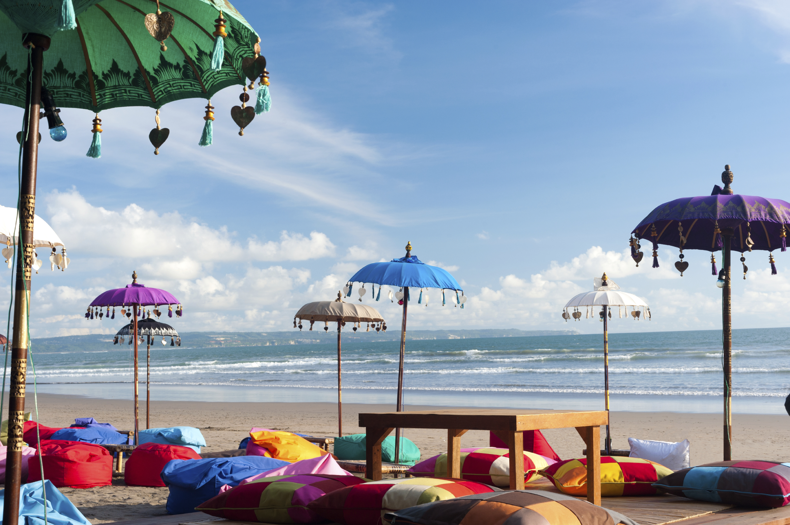 This image shows some colourful beach umbreallas and pillows in Kuta, Bali